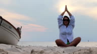 Woman in shirt meditating on a beach near a sea and a boat video
