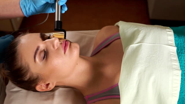 Woman in spa salon, facial rejuvenation procedure. Visit of a beautician. video