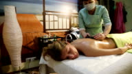 Woman in spa salon with hot stones video