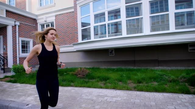 Woman in sportswear in motion of running on street in summer video