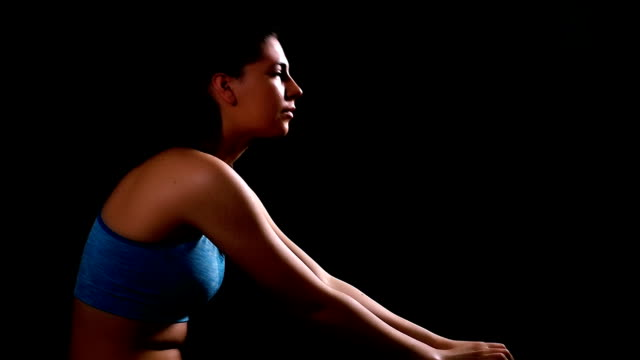 Woman in sportswear taking breath tired exhausted disappointed, black background, slow motion video