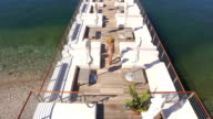 AERIAL: Woman in summer dress walking to the end of wooden jetty on sunny day video