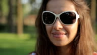 Woman in sunglasses in park video