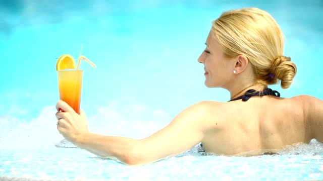 Woman in swimming pool having a cocktail. video