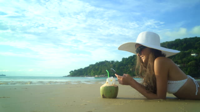 Woman In Swimsuit With Coconut Cocktail Laying On The Beach video