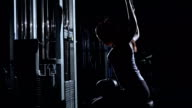 Woman in the gym doing pulldown exercises to back in silhouette video