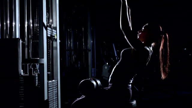 Woman in the gym doing pulldown exercises to front in silhouette video