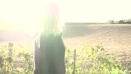 Woman in the morning before brown field with Sunflare video