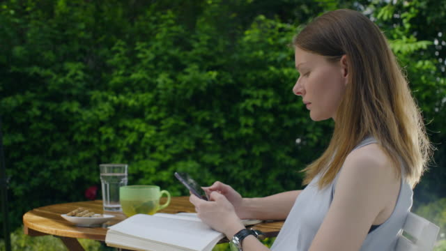 Woman in the yard reads the book and uses the mobile phone video