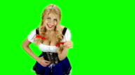 Woman in traditional costume offers a glass of beer on oktoberfest. Green screen video