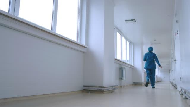 Woman in uniform running in white corridor back view. Urgent work video