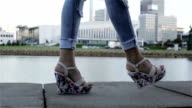 A woman in wedges and ripped jeans walking. Side view. Slow motion. video