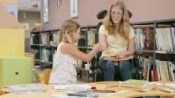 DS Woman in wheelchair handing crayons to girl in library video