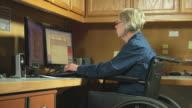 woman in wheelchair working office video