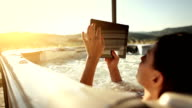 Woman in whirlpool jacuzzi with digital tablet video