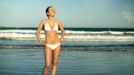 Woman in white bikini standing on the beach, slow motion video
