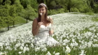 SLOW MOTION: Woman in white dress gathering flowers video