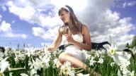 Woman in white dress gathering flowers video