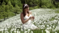 SLOW MOTION: Woman in white dress on a daffodil field video