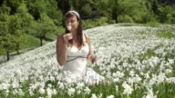SLOW MOTION: Woman in white dress smelling flowers video