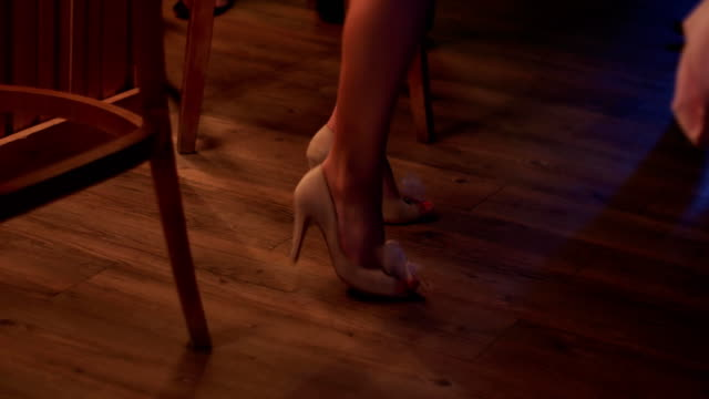 Woman in white mini dress, shoes on heels dance on party in nightclub. Holidays video