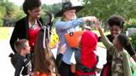 Woman in witch hat giving candy to trick or treaters video