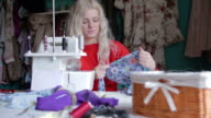 Woman in workshop sewing clothing video