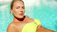 Woman in Yellow Bikini Suntanning Beside Pool video