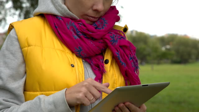 Woman in yellow vest using tablet pc in the park video