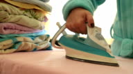 Woman ironing clothes with a steaming iron video