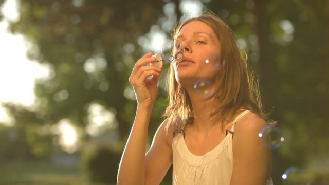 Woman is blowing soap bubbles video