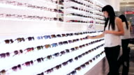 Woman is choosing a pair of sunglasses in optic shop video