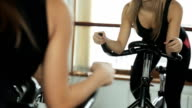 Woman is engaged on a stationary bike, gripping handlebar with your hands and not touching seats video