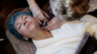 A woman is getting a mesotherapy of her face video