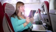 Woman is having video call over palmtop on the plane video
