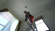 Woman is installing light in the house video