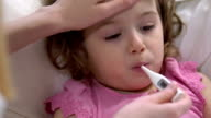 Woman is measure the temperature of little girl. video
