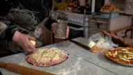 A woman is preparing a homemade pizza on the kitchen table at home. video