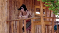 woman is relaxing in a windy day of summer leaning against a railing of wood video