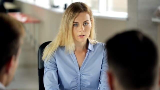Woman is sitting in office having work interview or meeting video