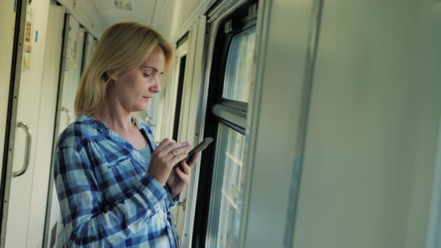 A woman is standing by the window in the corridor of a passenger railway car. Uses a mobile phone video