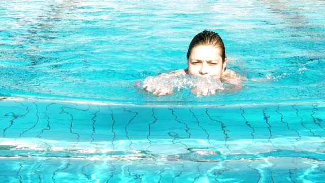 Woman is swimming in a pool on a bright summer day video