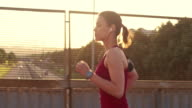 SLO MO Woman jogging across a highway overpass in sunset video