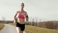 SLO MO TS Woman jogging along a road video
