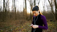 Woman jogging and using the smart phone. video