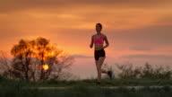 SLO MO TS Woman jogging at sunset video