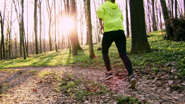 SLO MO TS Woman jogging in a spring forest at sunset video