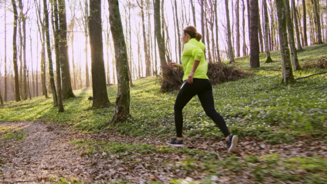 SLO MO TS Woman jogging in a spring forest on a beautiful sunny day video