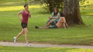 SLO MO TS Woman jogging through the park video