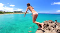Woman jumping from cliff into the ocean video